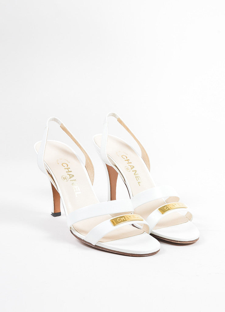 White and Gold Toned Chanel Leather Strappy Logo Plate Slingback Sandals Frontview
