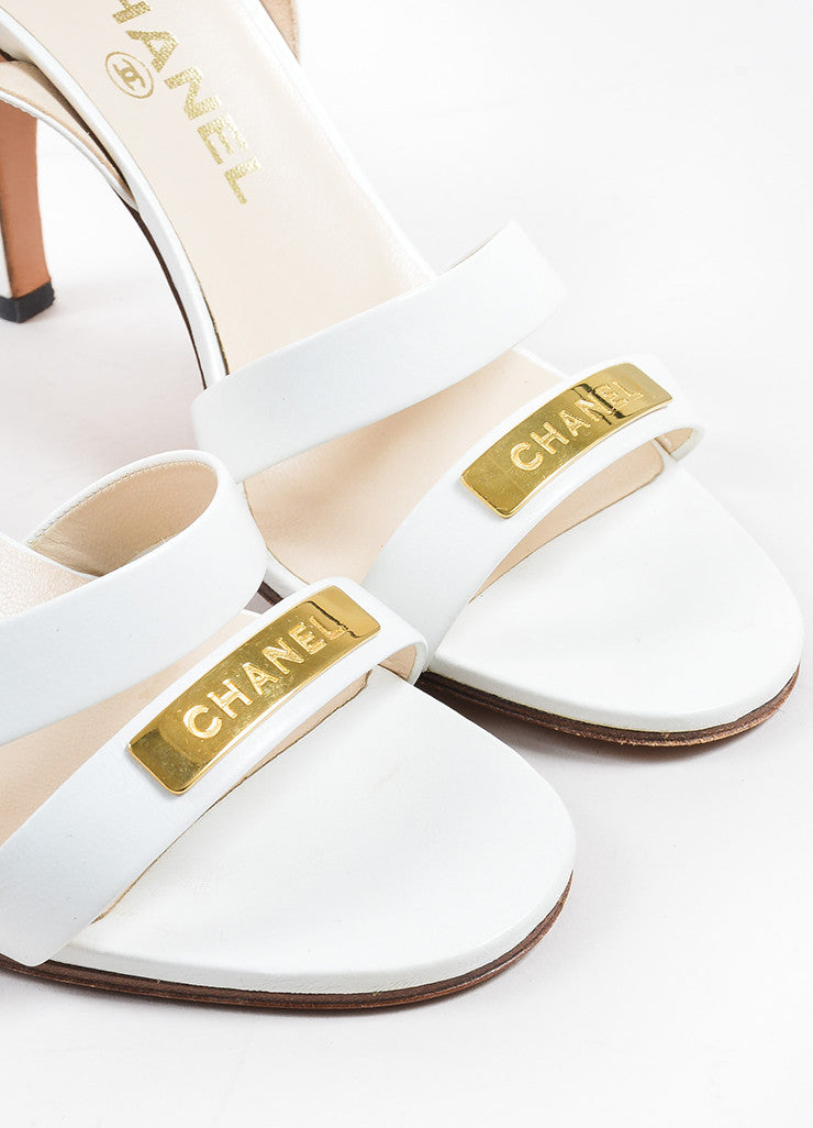 White and Gold Toned Chanel Leather Strappy Logo Plate Slingback Sandals Detail
