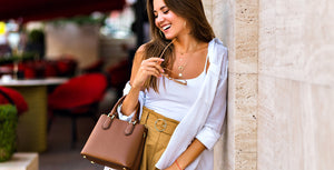 Fashionable woman smiling, holding a brown tote bag.