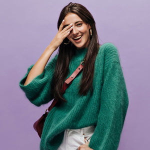 Trendy young woman wearing a green sweater, earrings and a handbag.