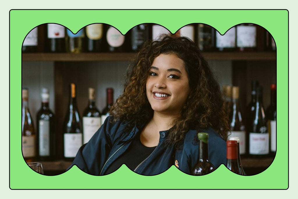 Portrait of April's host, Jirka, leaning on a bar with wine bottles in the background. In the foreground there are poured glasses of wine.