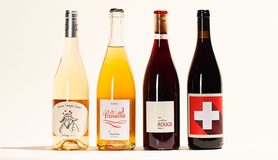 A line-up of four wine bottles. From left to right; a light rose with white label, an orange-colored wine with a crown cap, a red wine with its cork visible through the clear glass wine bottle, and a red wine with a red label.
