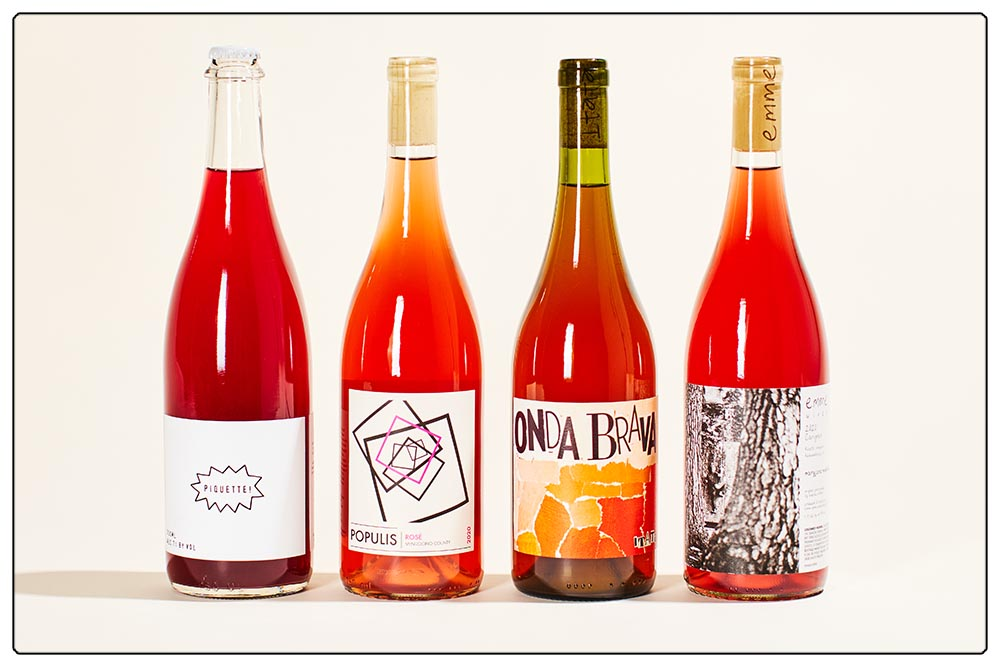 A line-up of rosy red colored wine bottles