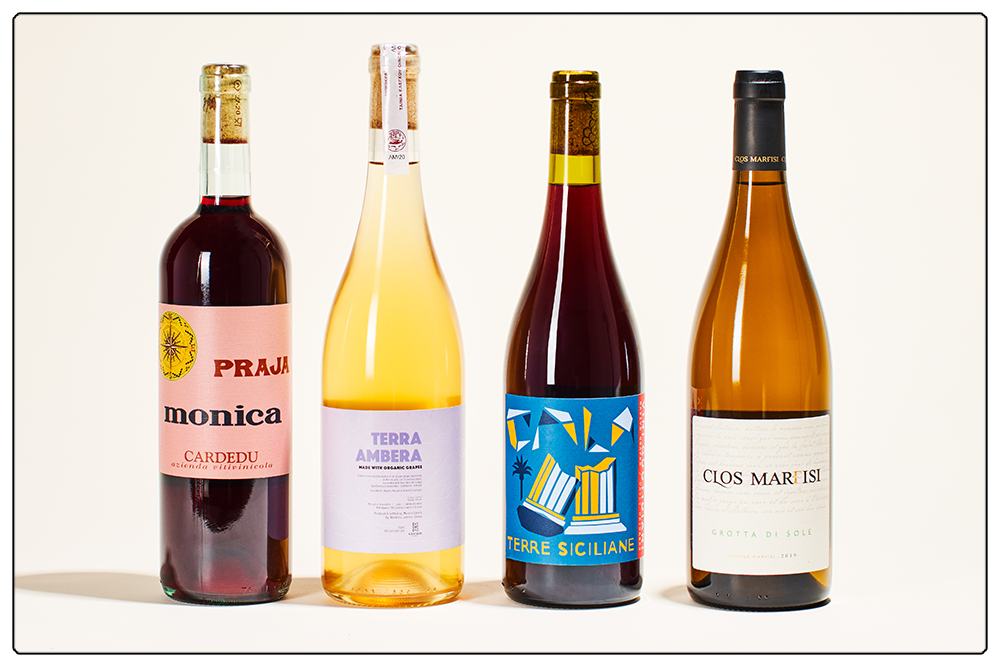 A line-up of March's bottles, from left to right a light red wine, a hazy orange wine, a darker red, and a bottle of white.