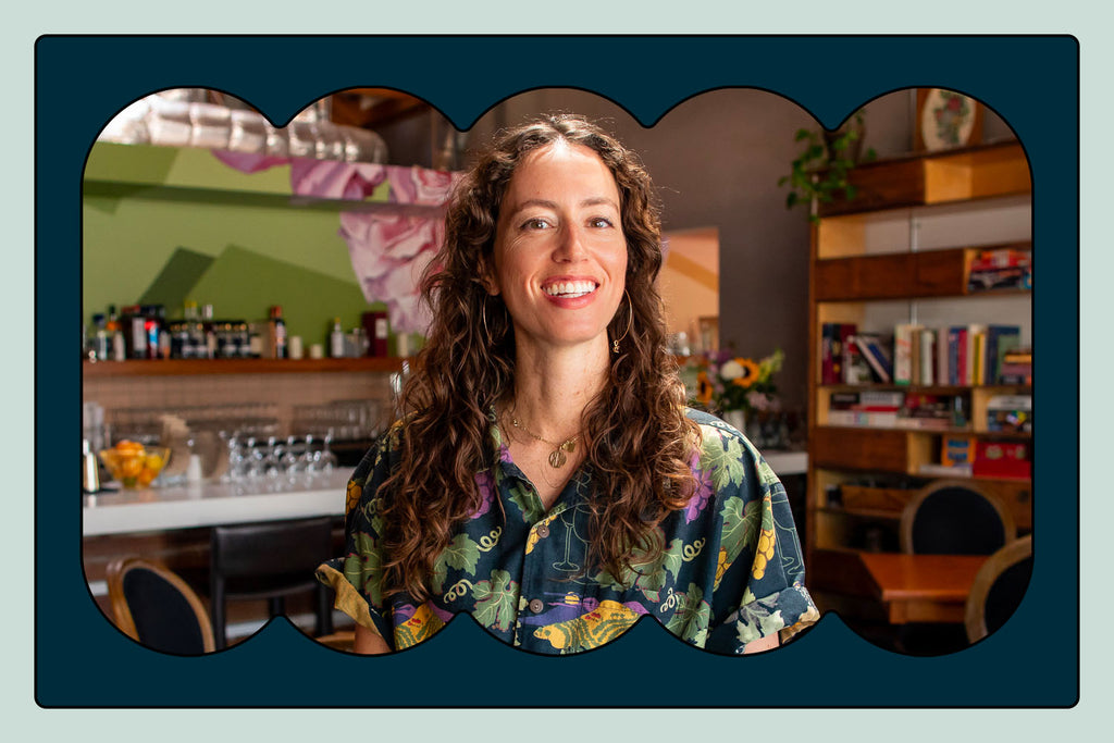 Portrait of somm Chelsea Coleman. A young female with long curly hair stands in front of a bar stocked with liquor and wine bottles. She is wearing a button down shirt with a fun Hawaiian-style print.