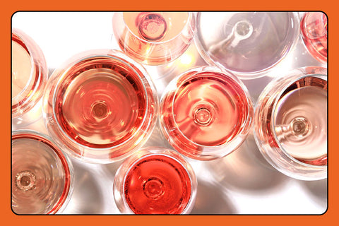 Overhead shot of wine glasses filled with red and rose wines of varying shades and depth of color.