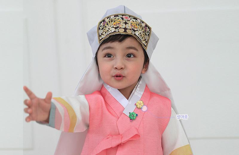 Young boy wearing a pink and gray korean hanbok