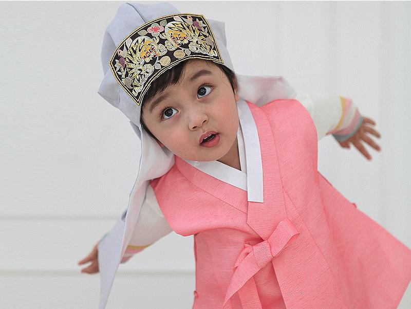 Young boy wearing a pink and gray korean hanbok and looking up