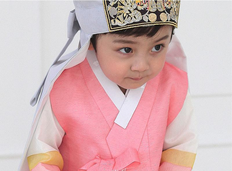 Young boy wearing a pink and gray korean hanbok with hat