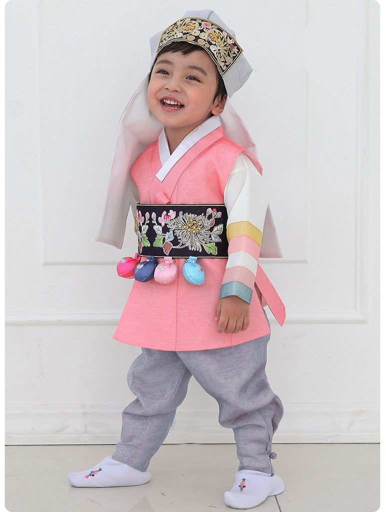 Young boy wearing a pink and gray korean hanbok and smiling