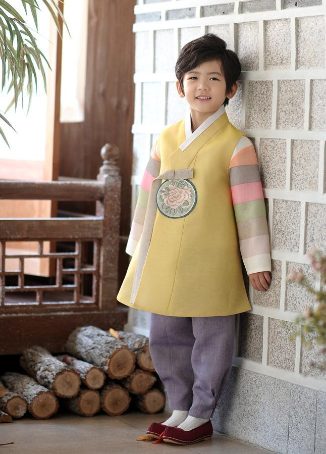 Young boy wearing a yellow and purple korean hanbok standing next to a wall