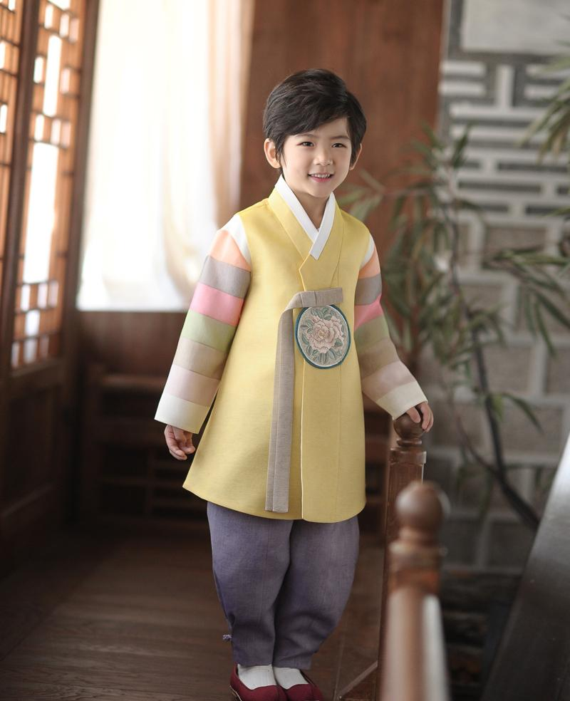 Young boy wearing a yellow and purple korean hanbok while smiling