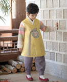 Young boy wearing a yellow and purple korean hanbok looking down
