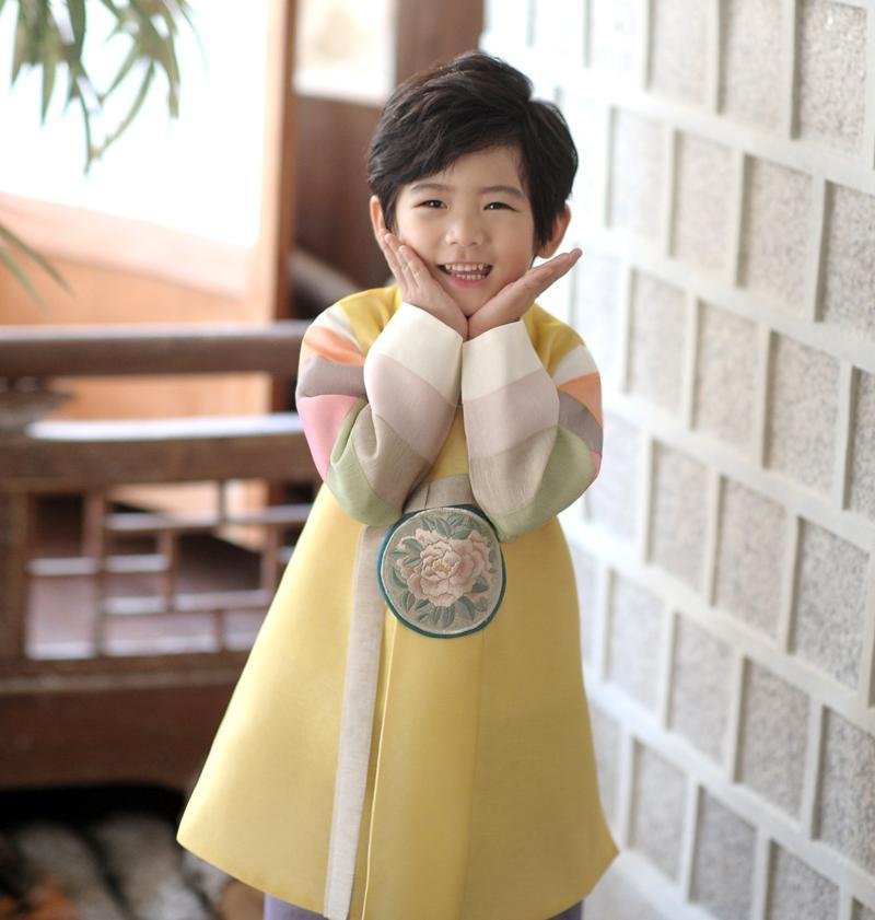 Young boy wearing a yellow and purple korean hanbok with cute smile