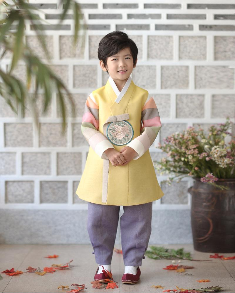 Young boy wearing a yellow and purple korean hanbok