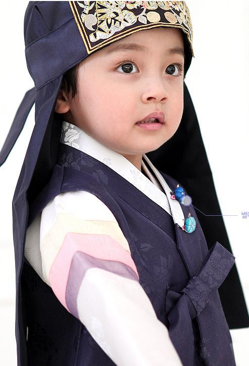 Young boy wearing a navy korean hanbok and looking up