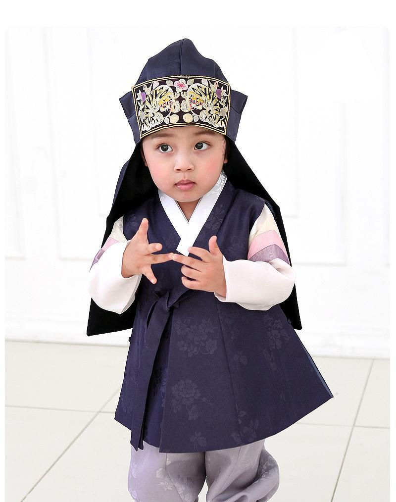 Young boy wearing a navy korean hanbok and touching fingers