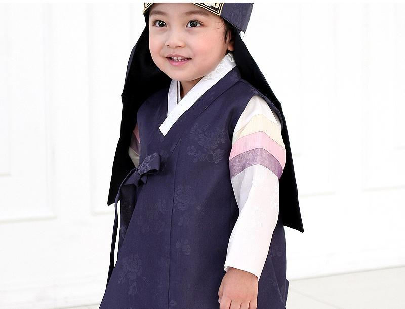 Young boy wearing a navy korean hanbok with hat and smiling