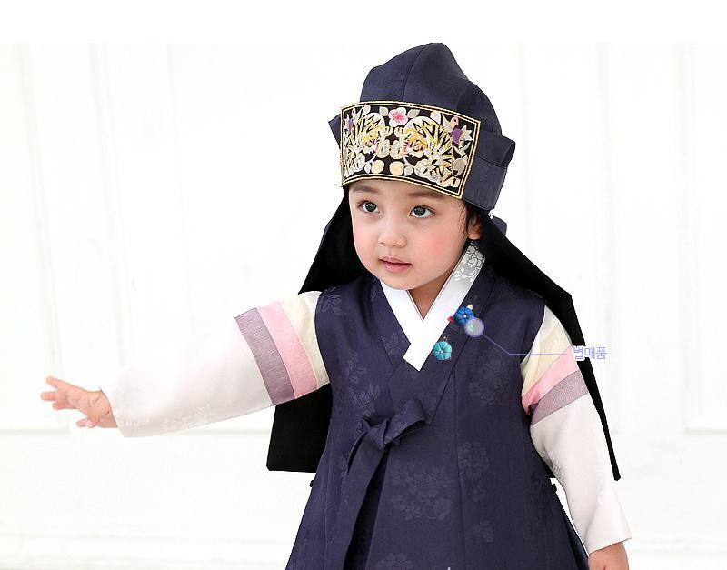 Young boy wearing a navy korean hanbok and holding out arm
