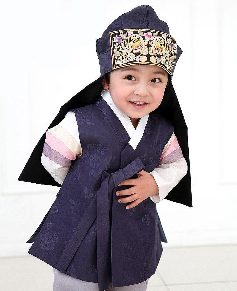 Young boy wearing a navy korean hanbok and bowing