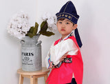 Young boy wearing a bright pink hanbok and navy hat posing next to flowers