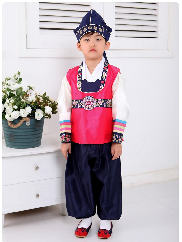 Young boy wearing a bright pink hanbok and navy hat standing next to flowers