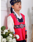 Young boy wearing a bright pink hanbok and navy hat and standing
