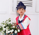 Young boy wearing a bright pink hanbok and navy hat