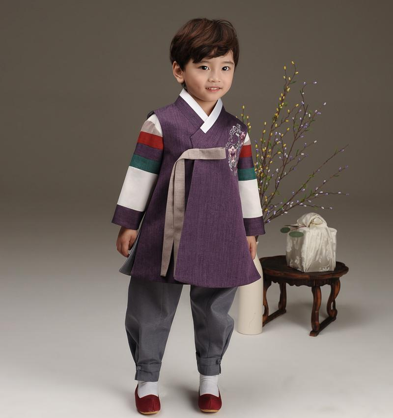 Young boy wearing a royal purple hanbok and looking over