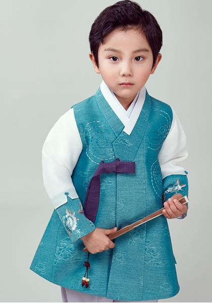 Young boy wearing a sky blue hanbok and holding a fan