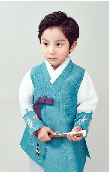 Young boy wearing a sky blue hanbok and holding a fan with two hands