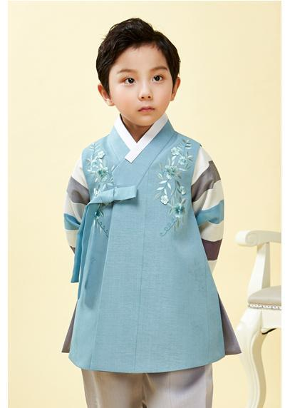 Young boy wearing a slate blue hanbok and arms behind his back