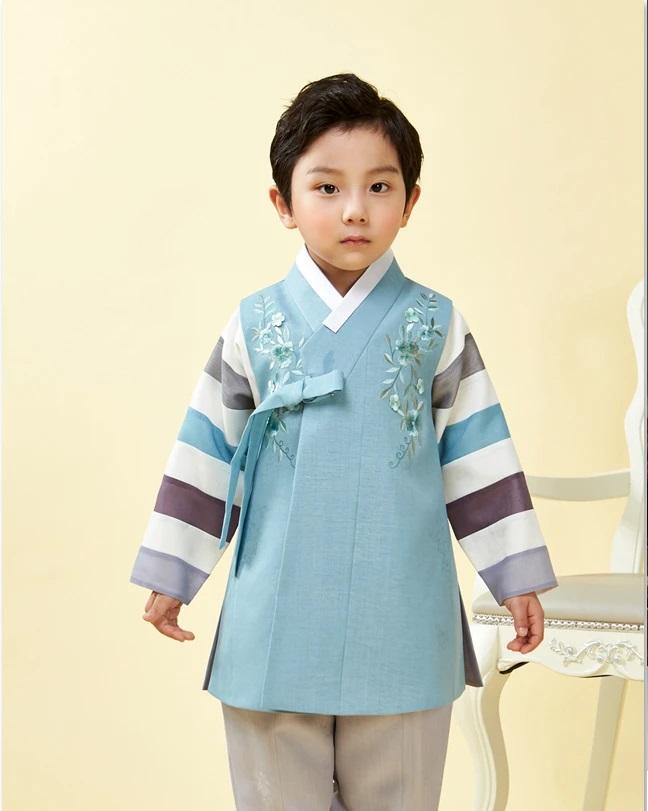 Young boy wearing a slate blue hanbok and arms out