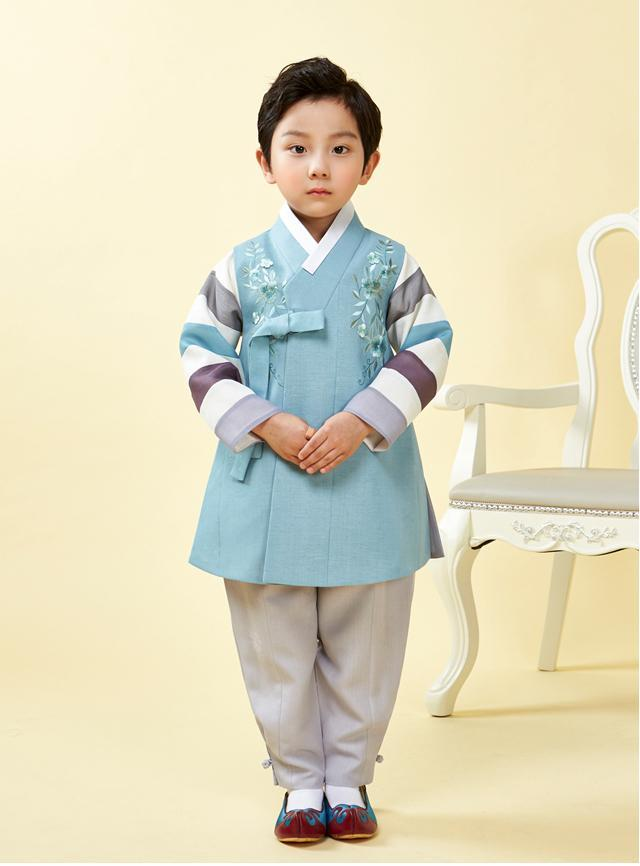 Young boy wearing a slate blue hanbok and clasping his hands