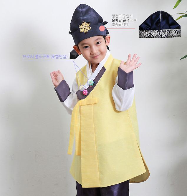 Young boy wearing a sunny yellow hanbok and blue hat