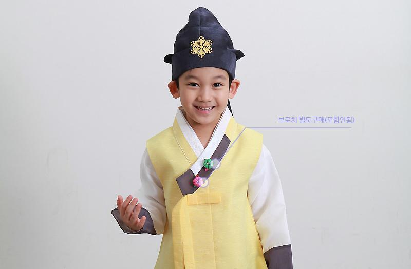 Young boy wearing a sunny yellow hanbok and blue hat and laughing