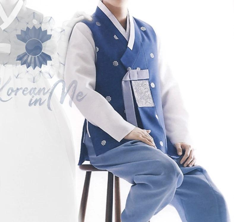 Man wearing custom grooms hanbok blue satin top and blue pants while sitting on chair