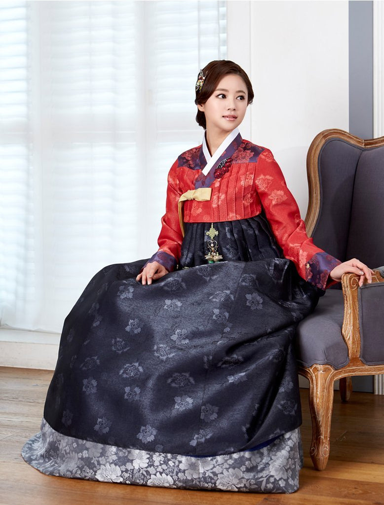 Woman wearing custom mother of the bride hanbok with red top and navy skirt while sitting down