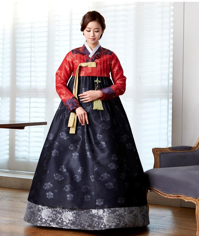 Woman wearing custom mother of the bride hanbok with red top and navy skirt looking down