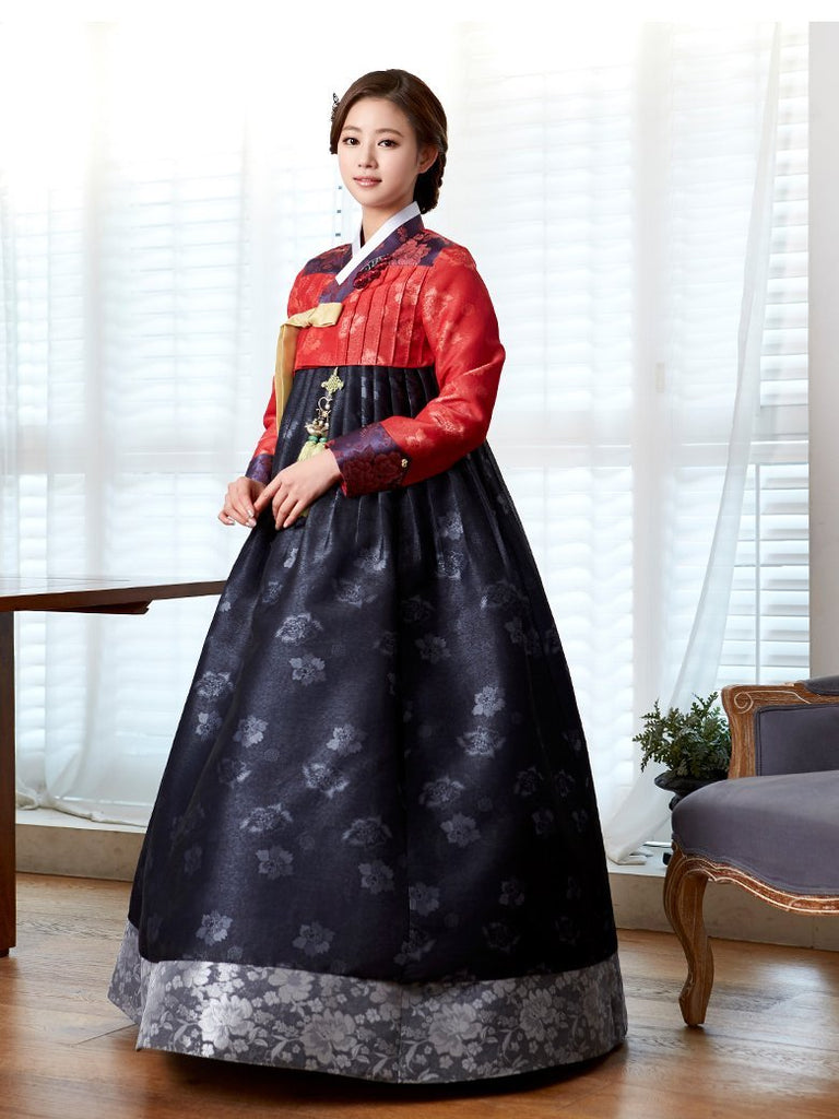 Woman wearing custom mother of the bride hanbok with red top and navy skirt