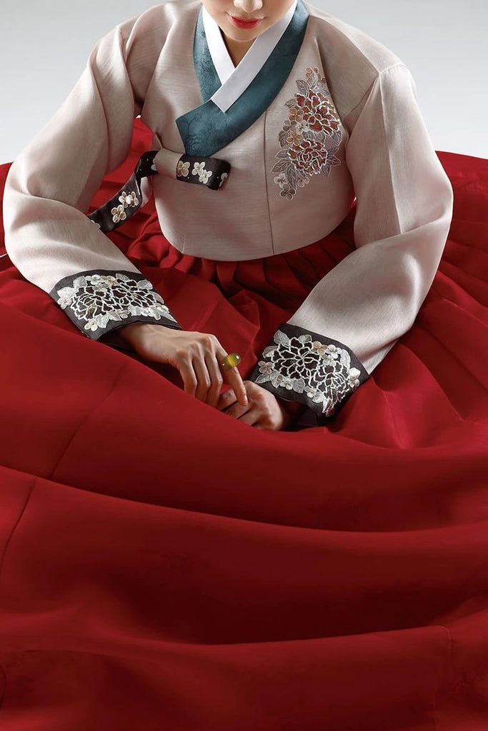 Woman wearing custom mother of the bride hanbok with red top and navy skirt sitting down