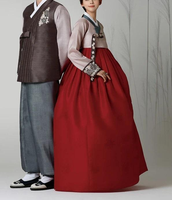 Woman wearing custom mother of the bride hanbok with rose top and red skirt standing next to a man