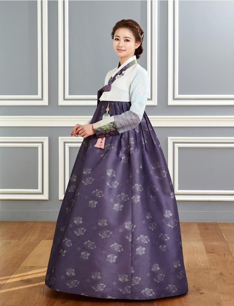 Woman wearing custom mother of the bride hanbok with white top and purple skirt and smiling