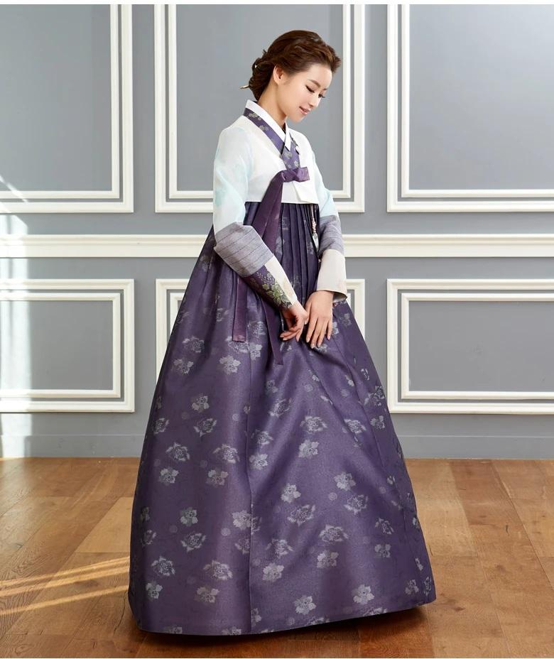 Woman wearing custom mother of the bride hanbok with white top and purple skirt and looking down