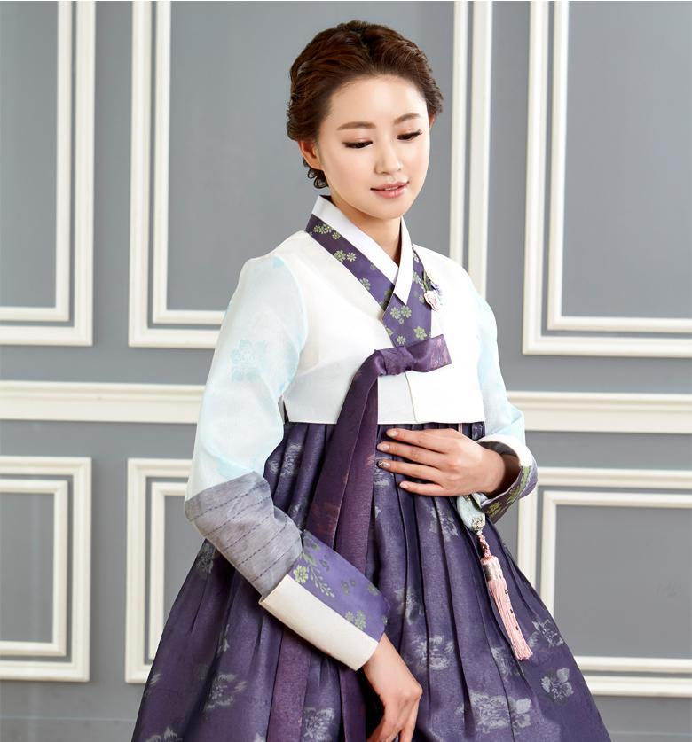Woman wearing custom mother of the bride hanbok with white top and purple skirt
