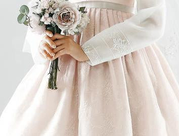 Closeup of womans hands as she wears a custom womens bridal hanbok in lace and pastel pink style
