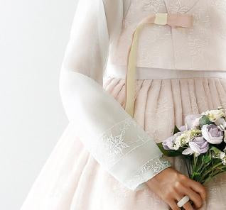 Closeup of sleeve of custom womens bridal hanbok in lace and pastel pink style