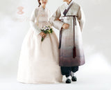 Woman wearing a custom womens bridal hanbok in lace and pastel pink style while with man