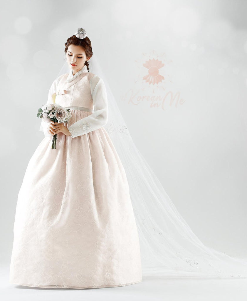Woman holding a bouquet and wearing a custom womens bridal hanbok in lace and pastel pink style