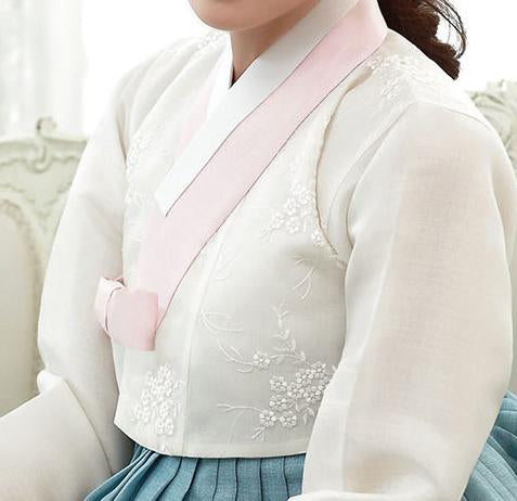 Closeup of woman sitting and wearing a custom womens bridal hanbok with white top and blue skirt